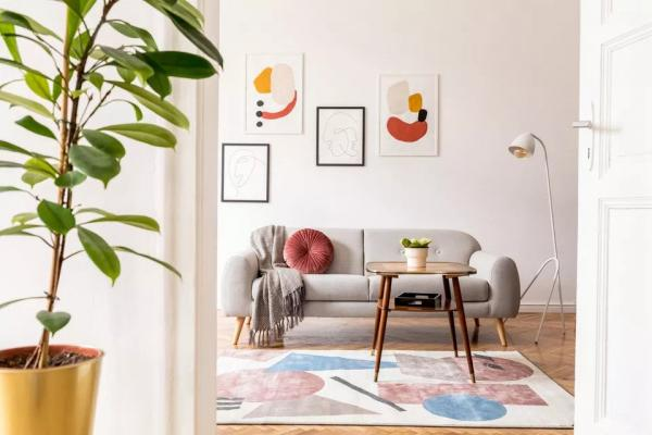 elegant-retro-living-room-with-design-grey-sofa--coffee-table--lamp--plants-and-furniture--mock-up-posters-frame-on-the-white-walls--minimalistic-room-with-brown-wooden-parquet-and-design-lamp--1132529156-b55774c.jpg