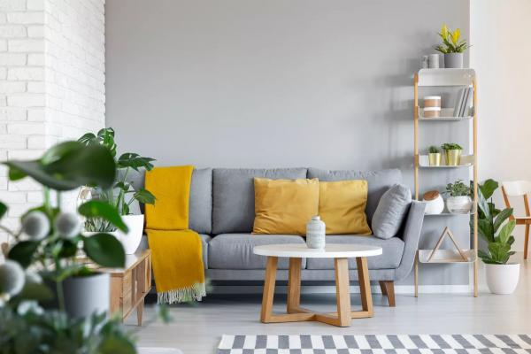 orange-pillows-and-blanket-on-grey-couch-in-living-room-interior-with-wooden-table--real-photo-1000701162-e3e8b1a1e880472da8ac9be1413600f0.jpg